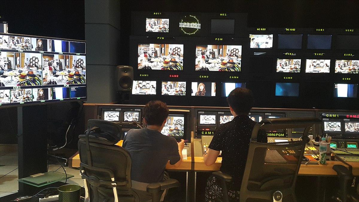 부조정실에서 녹화 장면을 확인하는 연출자(왼쪽)와 기술감독(오른쪽) 왼쪽이 연출자이고, 오른쪽이 기술감독으로 콘솔이 오른쪽에 있고 카메라 컷을 넘기는 버튼이 왼쪽에 위치하고 있어 왼손으로 컷팅을 한다.