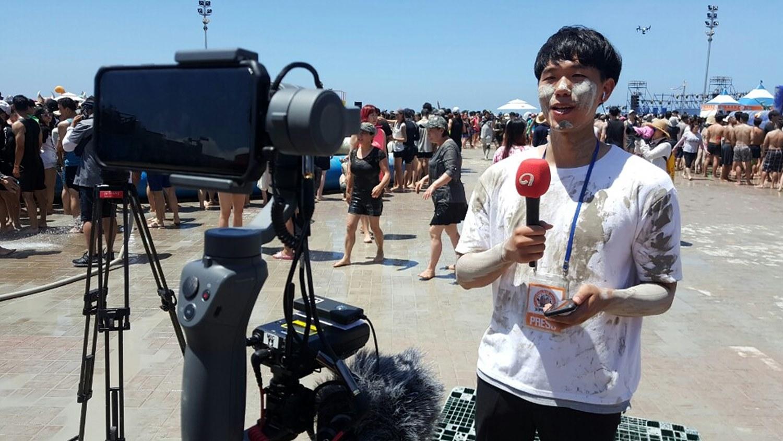 보령머드 축제에서 스마트폰으로 뉴스 생방송을 진행하는 장면